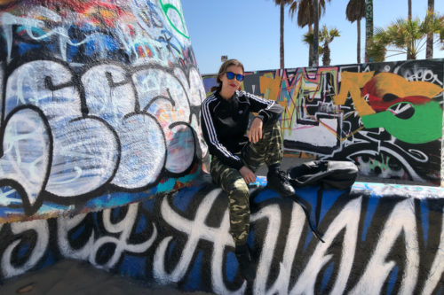Jente sitter på tagget mur