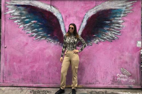 jente står foran rosa vegg med englevinger