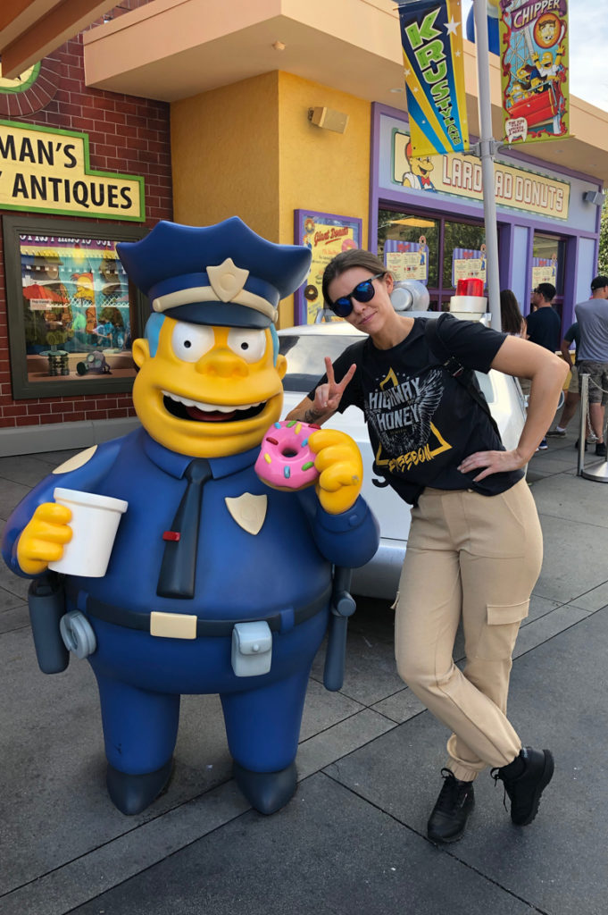 Jente poserer med en gul figur kledd i politiuniform