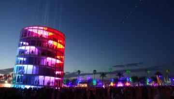 Tårn med fargerike lys og grønne palmer som lyses opp i nattmørket