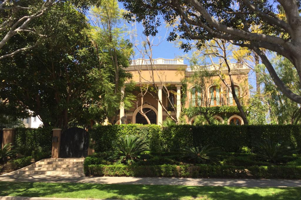 Gult mursteinsbygg bak en grønn hekk og et stort tre