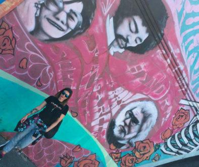 Jente poserer foran en vegg tagget med grafitti